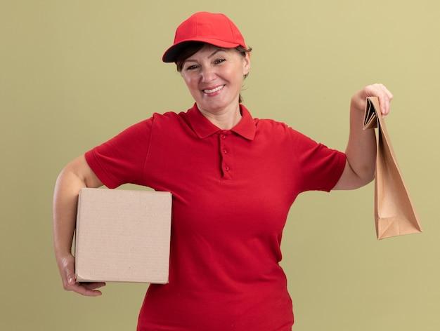 Felice donna di mezza età consegna in uniforme rossa e cappuccio che dà pacchetto di carta e scatola di cartone guardando la parte anteriore sorridente allegramente in piedi sopra la parete verde