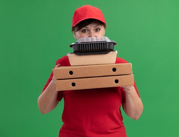 Felice donna di mezza età consegna in uniforme rossa e cappuccio che tiene scatole per pizza e confezioni di cibo guardando davanti in piedi sopra la parete verde
