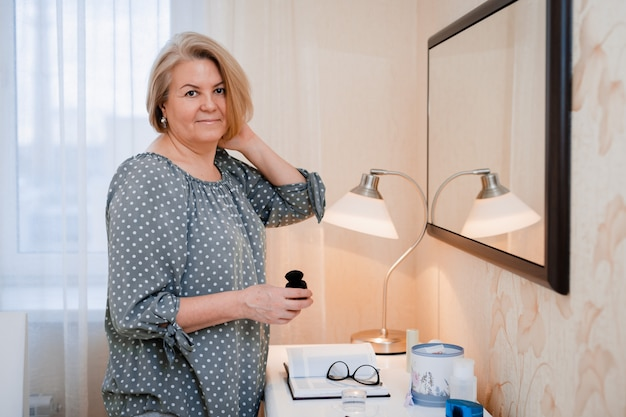 Happy middle aged elderly woman preens and adjusts her hair in front of the mirror of the dressing table
