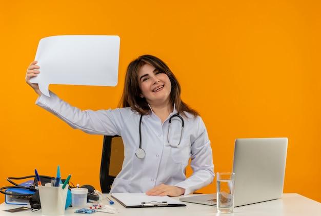 의료 가운과 청진기를 입고 의료 도구 클립 보드와 노트북 채팅 거품 격리를 들고 책상에 앉아 행복 한 중년 여성 의사