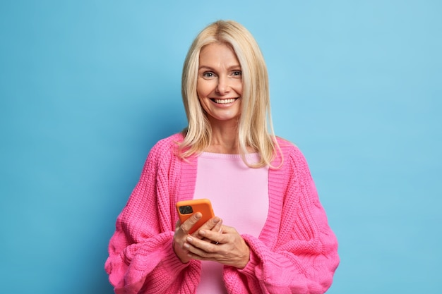 Happy middle aged lady holds mobile phone glad to read pleasant sms chats with friends in social networks wears warm knitted jumper stands indoor. elderly technology concept. modern grandmother