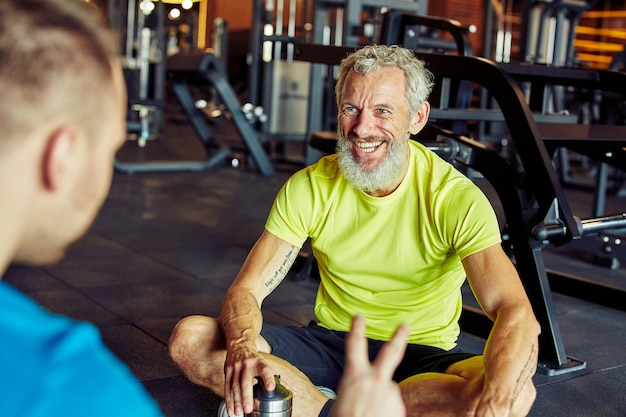 Happy middle aged man discussing something with fitness instructor or personal trainer and smiling