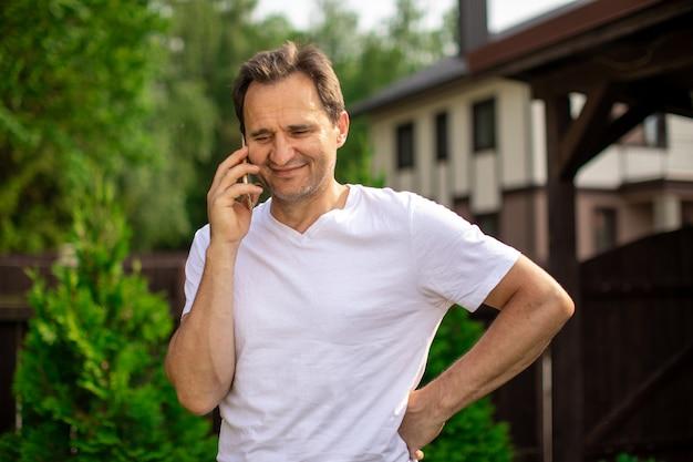 スマートフォンで話している幸せな中年男性、携帯電話で夏の晴れた日に屋外に立っているフレンドリーな男性を笑顔。コピースペース、コミュニケーション、デジタルピープル、携帯電話会社の広告コンセプト