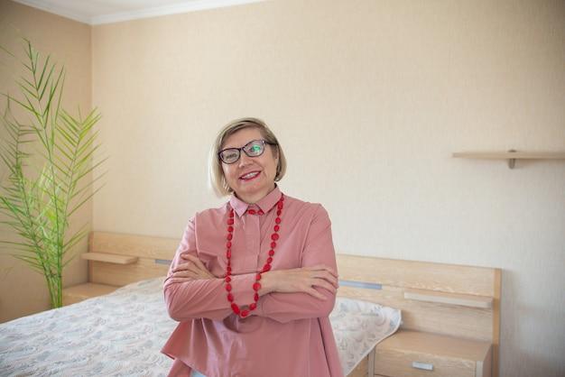 Счастливая зрелая седая женщина среднего возраста с седыми волосами, улыбающаяся старуха в очках у себя дома, позитивная одинокая женщина-пенсионерка