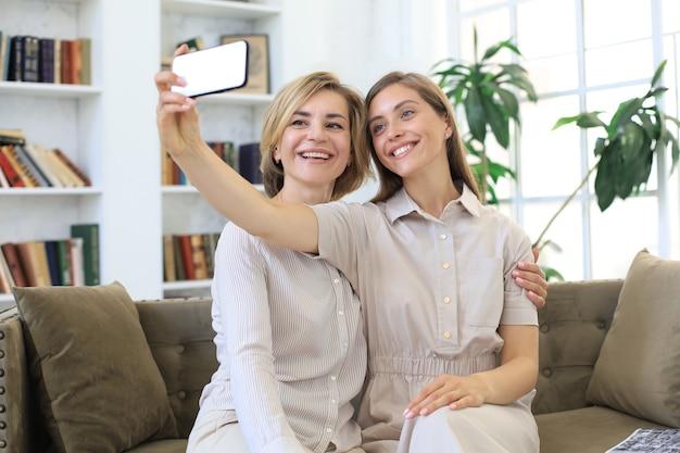 행복한 중년 엄마와 딸이 집에서 셀카를 찍고 있습니다.