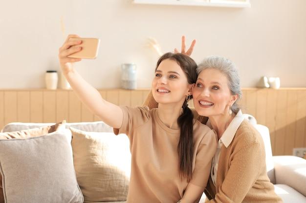 Счастливая мать и дочь среднего возраста, делающая селфи дома.