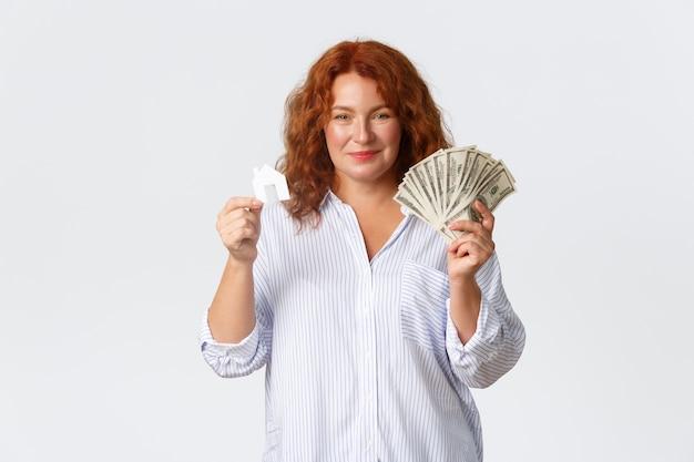 Счастливая рыжая дама средних лет показывает деньги, доллары и карточку дома