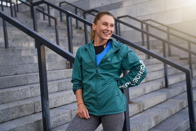 朝のトレーニングの後に屋外に立って微笑んでいるスポーツウェアの幸せな中年のスポーツウーマン