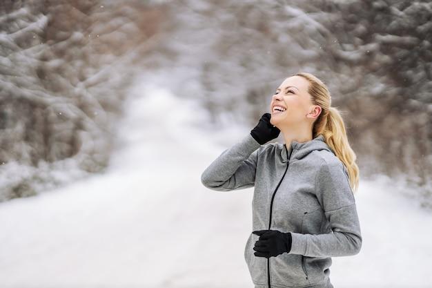 겨울에 자연의 눈 덮인 길에 서서 전화를 받는 행복한 중년 스포츠우먼. 건강한 생활, 통신, 겨울 피트니스