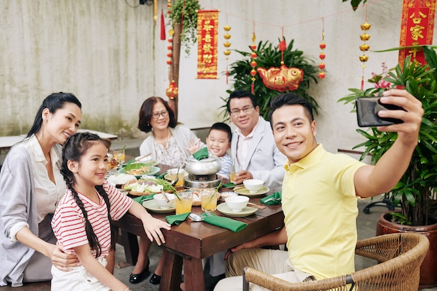 Happy middle-aged vietnamese man taking selfie with his big family at lunar new year celebration