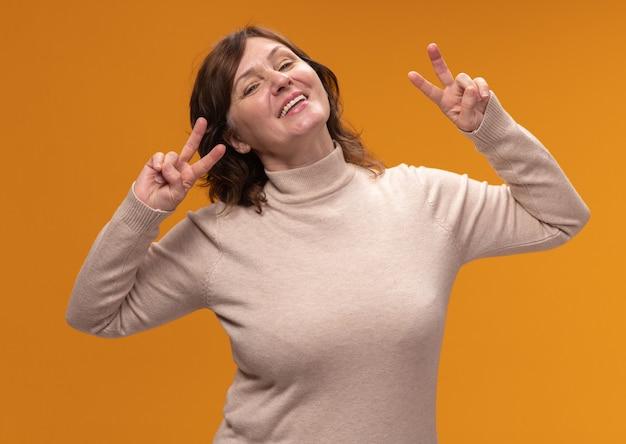Felice donna di mezza età in dolcevita beige che sorride allegramente mostrando v-segno in piedi sopra la parete arancione