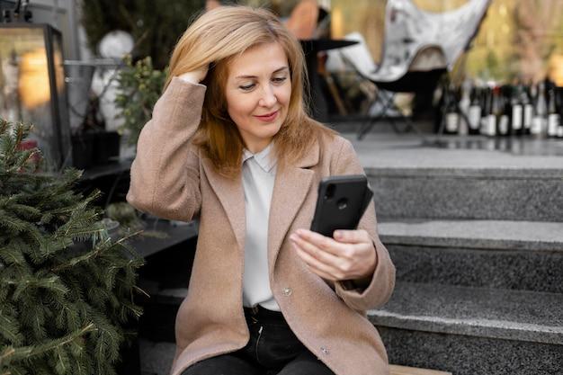 Счастливая женщина средних лет проверяет свой телефон