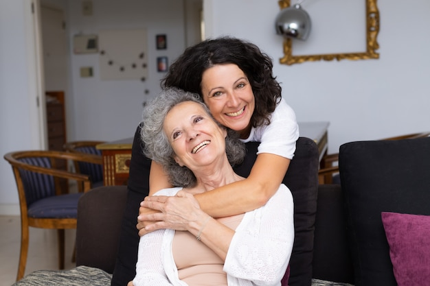 Happy middle aged woman hugging senior lady
