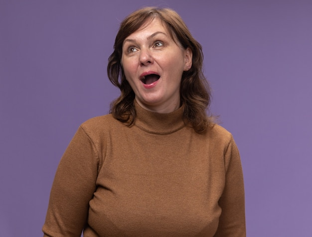 紫色の壁の上に立って幸せで陽気な見上げる茶色のタートルネックの幸せな中年女性