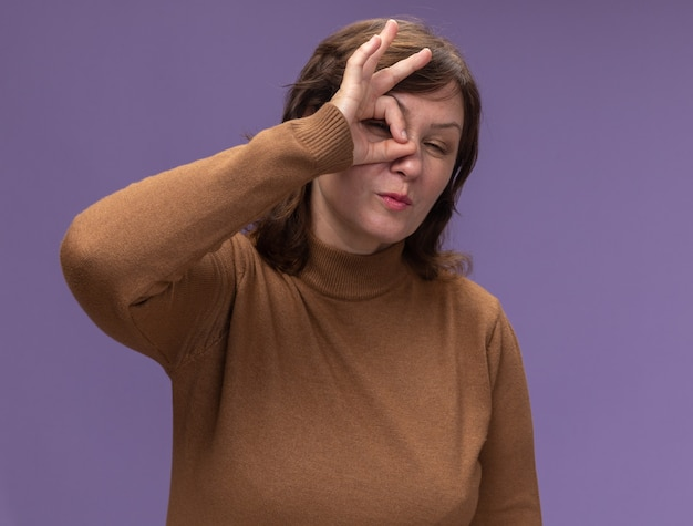 Счастливая женщина средних лет в коричневой водолазке делает знак ок, глядя сквозь этот знак, подмигивая, стоя над фиолетовой стеной