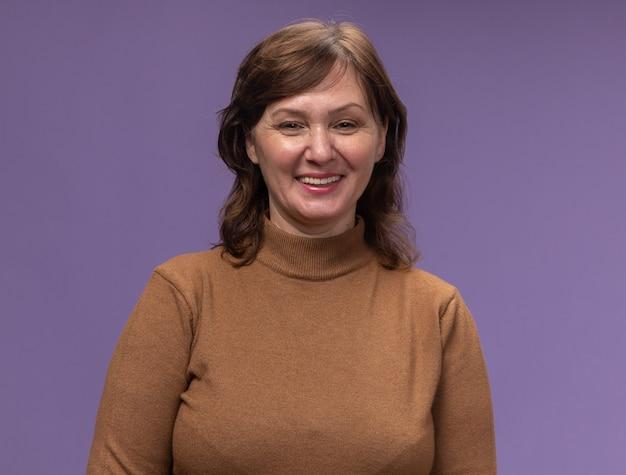 紫色の壁の上に広く立って笑っている茶色のタートルネックの幸せな中年女性