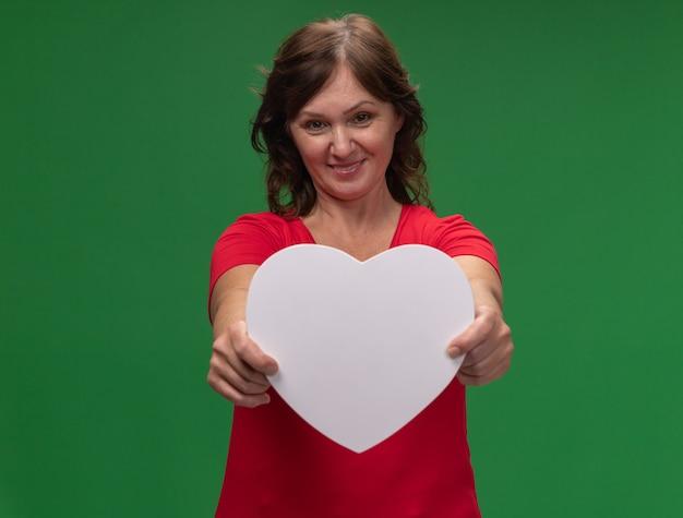 緑の壁の上に元気に立って笑顔の段ボールの心を示す赤いtシャツで幸せな中年女性