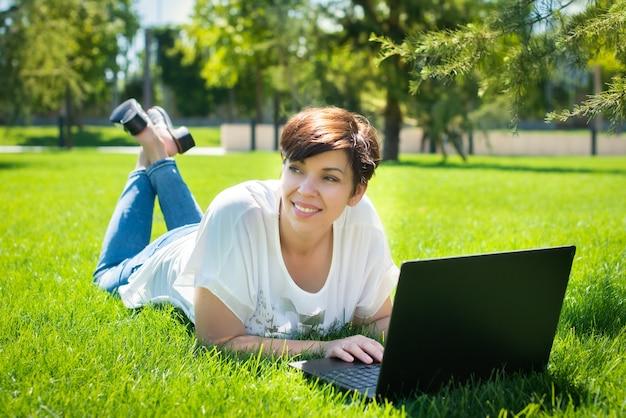 公園でラップトップコンピューターを使用して緑の草の上に横たわる幸せな中年の女性。大人の男が屋外で実行します。オンラインでのビジネスとトレーニング。友達とチャット。
