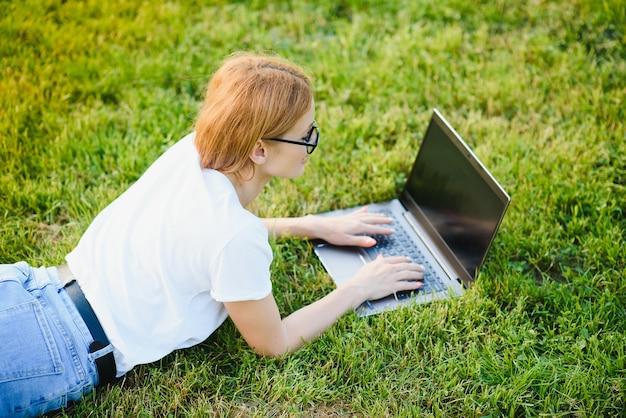 公園でラップトップコンピューターを使用して緑の芝生の上に横たわって幸せな中年女性