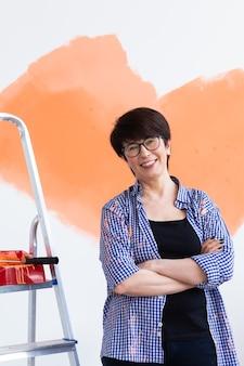 새 집에 페인트 롤러와 인테리어 벽 그림 행복 한 중 년 여자. 롤러를 가진 여자