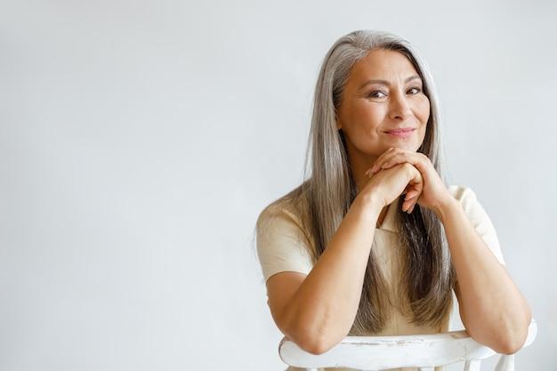 은색 머리를 한 행복한 중년 여성은 밝은 배경에 손을 기대고 앉아 있다