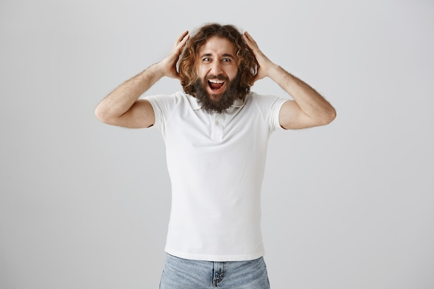 Happy middle-eastern bearded man react to good news excited