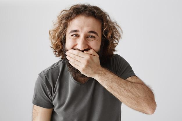 Счастливый парень с ближнего востока жует рот рукой и смеется, радостно улыбаясь