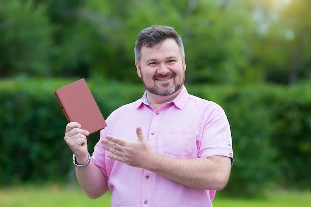 喜びと赤いシャツを着た幸せな中年の白人男性が新しい本を示しています