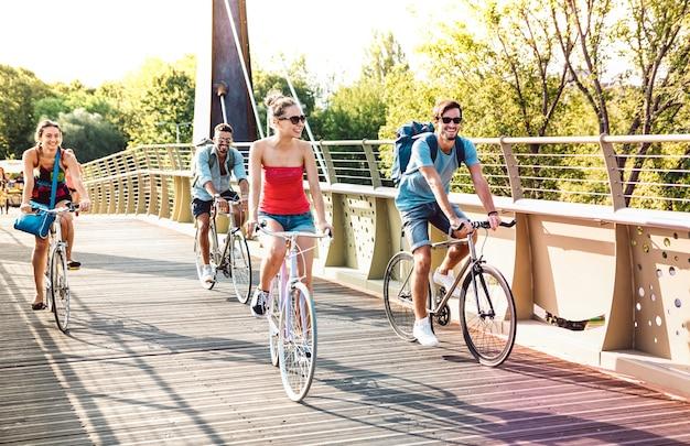 Happy milenial friends having fun riding bike at city park bridge