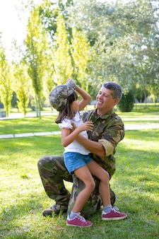 Happy military father hugging daughter after returning from mission trip. girl trying on dads camouflage cap. family reunion or returning home concept