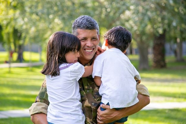 Felice padre militare incontro con i bambini dopo il viaggio di missione militare, tenendo i bambini in braccio e sorridendo. ricongiungimento familiare o concetto di ritorno a casa