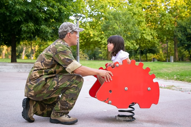 Happy military father spending time with daughter in playground, while girl riding spring rocking hedgehog. parenthood or childhood concept