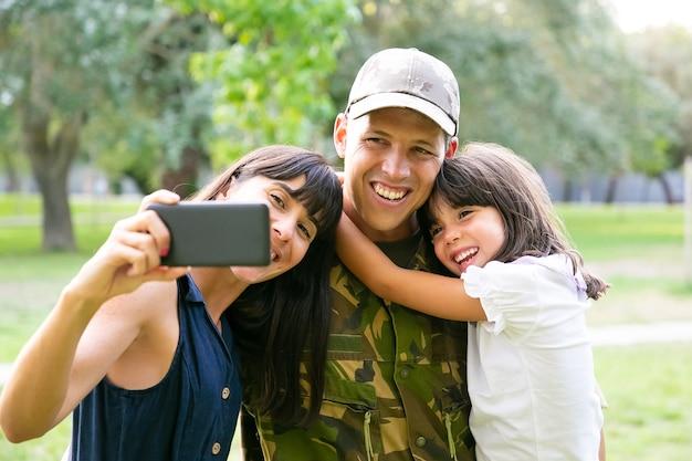 幸せな軍人、彼の妻と小さな娘が都市公園で携帯電話で自分撮りをしています。正面図。家族の再会または帰国の概念