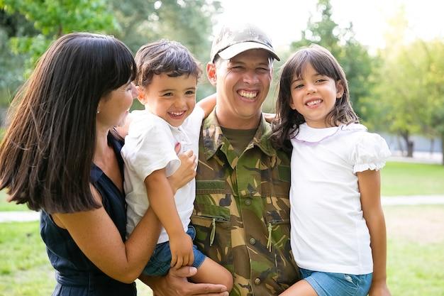 幸せな軍人が家族と一緒にポーズをとり、子供たちを腕に抱き、妻が子供たち全員を抱き締めて笑っています。ミディアムショット。家族の再会または帰国の概念