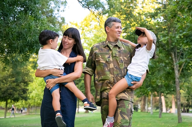 Happy military man walking in park with his wife and kids, teaching daughter to make army salute gesture. full length, back view. family reunion or military father concept