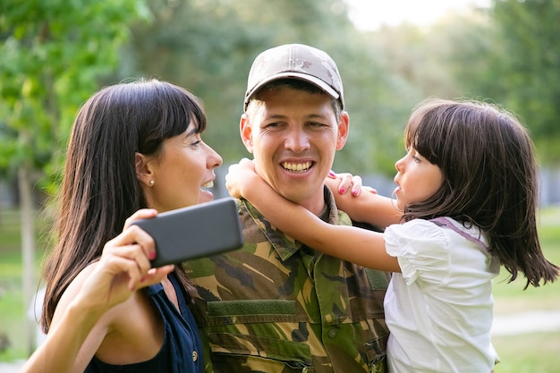 Happy military man with wife and little daughter taking selfie on cellphone in city park. front view. family reunion or returning home concept