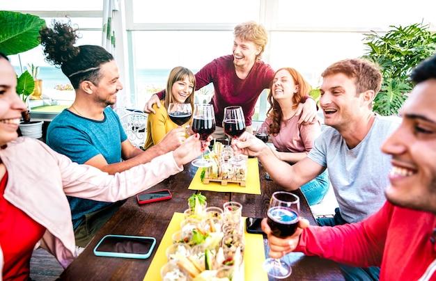 테라스에서 와인을 함께 마시는 행복한 천년 사람들