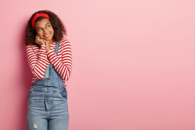 幸せなミレニアル世代のアフリカ系アメリカ人の女の子は、脇に幸せそうに見え、赤いヘッドバンド、ストライプのジャンパー、デニムのオーバーオールを着ています