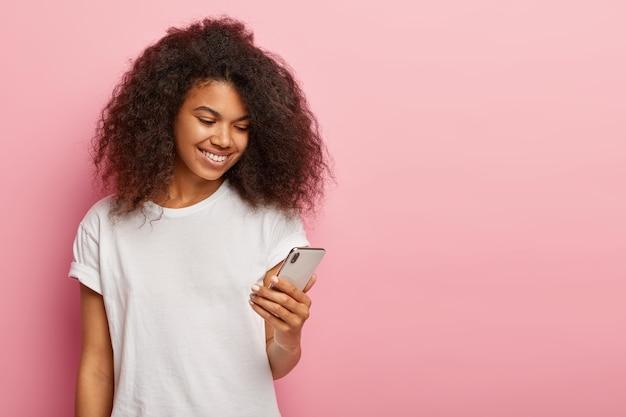 Felice millenaria donna afroamericana con riccioli scuri, guarda video divertenti su smart phone