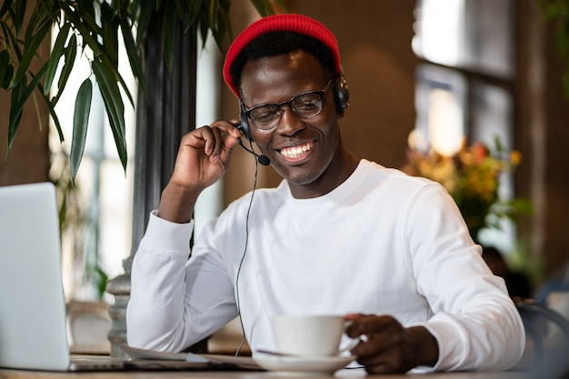 Happy millennial black man in headphones watching webinar on laptop, remotely online work in cafe, holding cup of coffee