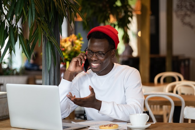 Happy millennial black man laughing, speaking with friend on mobile phone, remote work in cafe.
