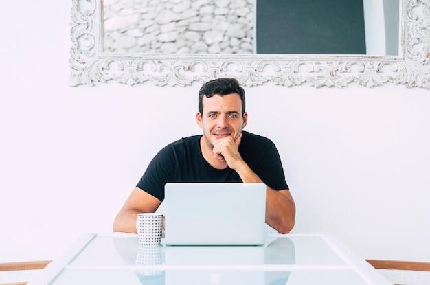 幸せなミレニアル世代のビジネスの若い男が、カメラに向かって微笑む現代のテクノロジー コンピューター ラップトップで机に座る