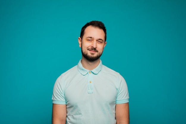 Happy millennial caucasian guy isolated on blue studio background smiling with white healthy teeth, positive young man in casual clothes posing.