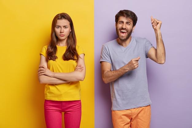 Счастливая пара миллениалов позирует у двухцветной стены