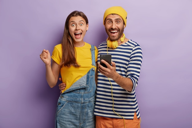 Happy millennial girl and boy embrace, have fun, hold mobile phone, watch funny video online, hug and smile happily
