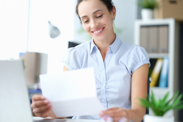 幸せなミレニアル世代の女の子のサイトは、郵便書類の手紙で良いニュースを読んで興奮していると感じています