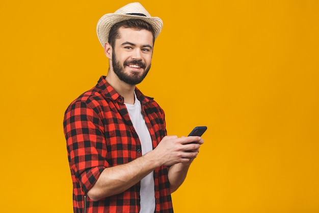 Happy millennial man holding smartphone checking or reading, smiling young male client customer using cellphone typing message or communicating.