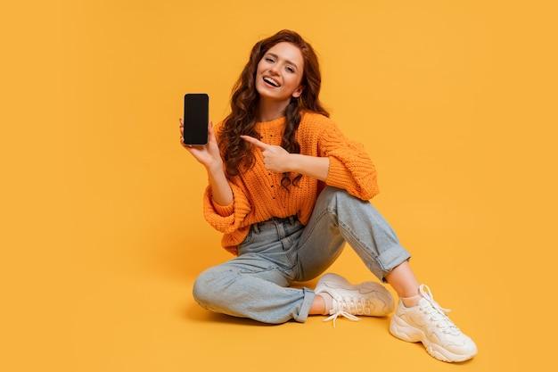 Felice donna millenaria che mostra lo schermo dello smartphone e punta su di esso