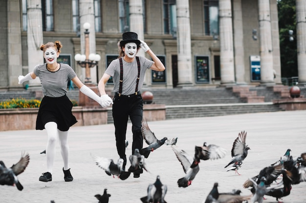 Happy mime couple running near flying pigeons