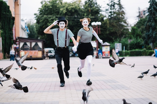 Happy mime couple running on pavement